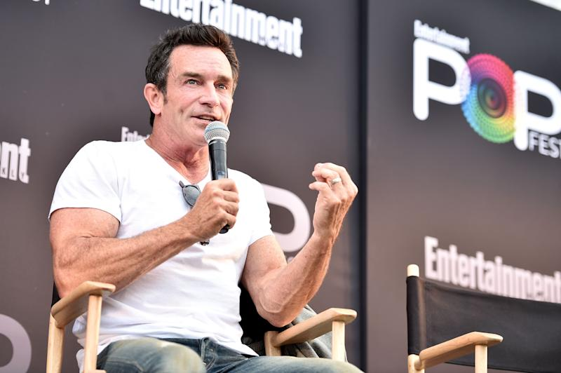 Jeff Probst speaks into a microphone while sitting in a directors chair