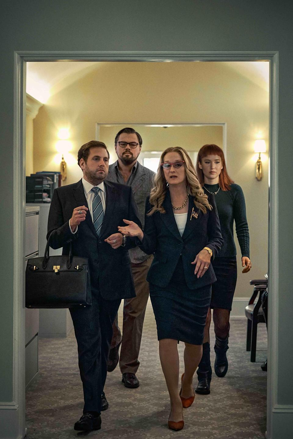 Meryl's character walking through a hallway as Jonah, who's holding her purse, follows along with Leo and Jennifer