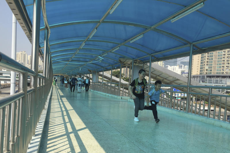 """In this Friday, Nov. 15, 2019 photo, children run across a pedestrian bridge leading from Hong Kong at the Huanggang Port in Shenzhen in southern China's Guangdong Province. Since anti-government demonstrators in Hong Kong began barricading university campuses earlier this week, hundreds of mainland Chinese students have retreated to neighboring Shenzhen, where the ruling Communist Party's Youth League has promised them a """"warm home."""" (AP Photo/Yanan Wang)"""
