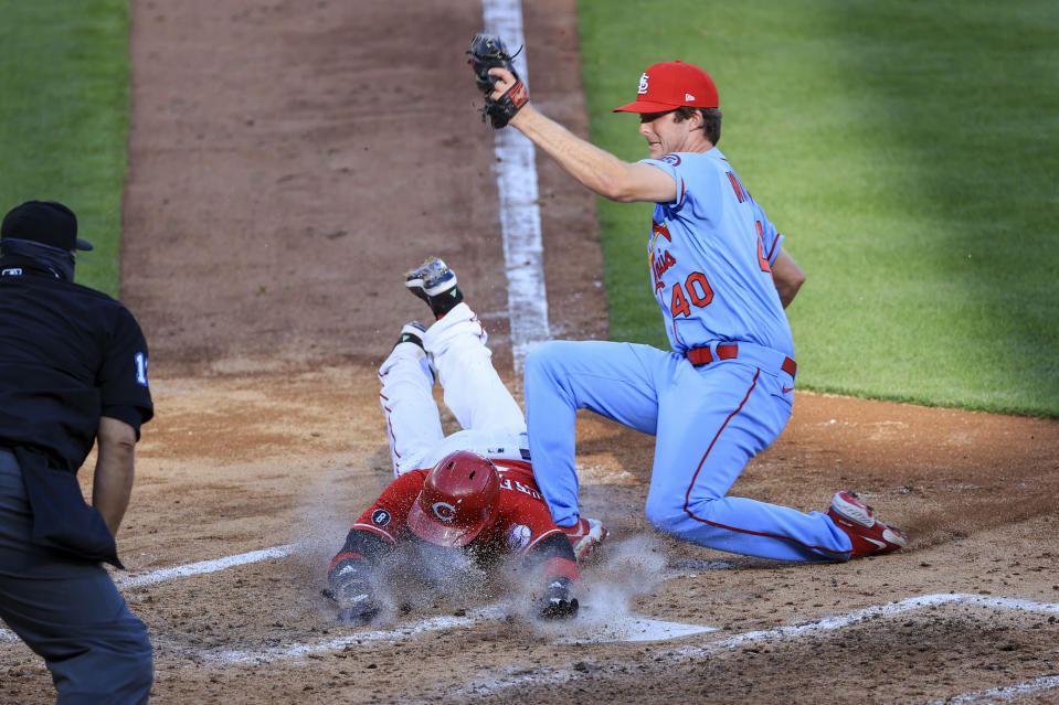 Cincinnati Reds' Nick Castellanos, center, scores a run ahead of the tag by St. Louis Cardinals' Jake Woodford, right, during the fourth inning of a baseball game in Cincinnati, Saturday, April 3, 2021. (AP Photo/Aaron Doster)