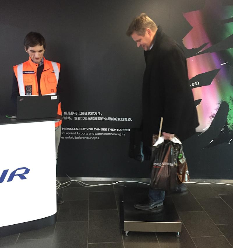 A Finnair pilot boards the scale with his carry-on bag at Helsinki Airport. He was one of some 180 volunteers to be weighed by the airline.