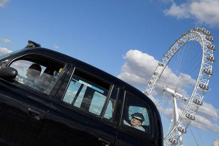 A taxi drives past the London Eye in central London