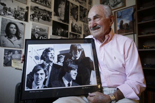 In this photo taken Friday, Aug. 1, 2014, retired news photographer and cameraman Fred Pardini holds a photo of the Beatles arriving in San Francisco in 1966, at his home in Alameda, Calif. Pardini photographed the early beginnings of Candlestick Park and the Beatles last concert there. Candlestick Park, known for its bone-numbing winds, the Catch and the earthquake-rocked 1989 World Series is officially closing after more than a half century of hosting sporting and cultural events. In a bow to historical symmetry, the Stick's finale will be a performance Thursday by Paul McCartney, 48 years after the Beatles' last scheduled concert lit up the venue. (AP Photo/Eric Risberg)