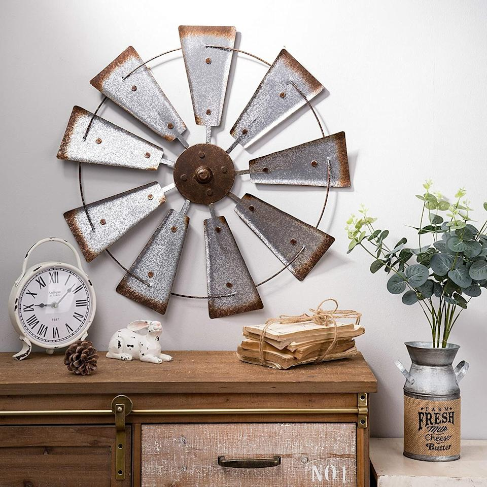 """If you're not into the now <a href=""""https://www.vox.com/the-goods/2020/4/27/21232688/sunburst-mirror-gold-diy-rattan"""" target=""""_blank"""" rel=""""noopener noreferrer"""">ubiquitous sunburst mirrors</a>, you might go for this windmill wall hanging that looks handmade. <a href=""""https://amzn.to/35dggFF"""" target=""""_blank"""" rel=""""noopener noreferrer"""">Find it for $36 at Amazon</a>."""