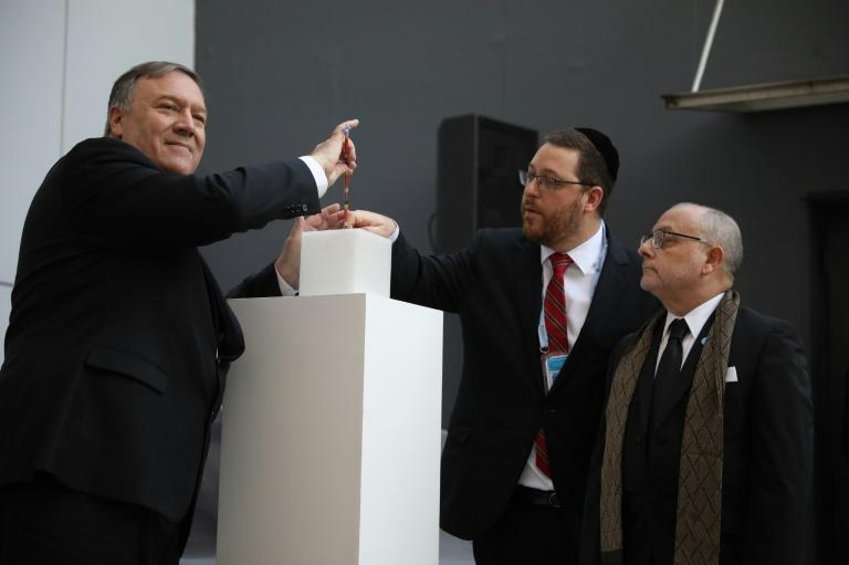 US Secretary of State Mike Pompeo lights a candle next to Argentine Foreign Minister Jorge Faurie and the president of the Asociacion Mutual Israelita Argentina (AMIA) Ariel Eichbaum to pay homage to the victims of a bombing at the center which left 85 people dead (AFP Photo/NATACHA PISARENKO)