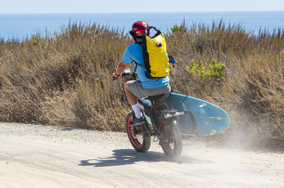 A surfer uses an electric bicycle to travel to Lower Trestles in San Clemente on Tuesday, August 27, 2019. (Photo by Leonard Ortiz/MediaNews Group/Orange County Register via Getty Images)
