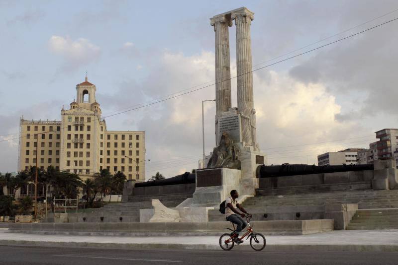 In this Tuesday, Feb. 12, 2013 photo, a youth rides his bicycle past the restored USS Maine monument in Havana, Cuba. The monument was erected in 1925 in honor of U.S. sailors who died in 1898 when the USS Maine ship sank off the Havana Harbor. The years since have been unkind to the twin-columned monument, and to U.S.-Cuba ties. But while relations between Washington and Havana remain in deep freeze, the monument, at least, is now getting a facelift. (AP Photo/Franklin Reyes)