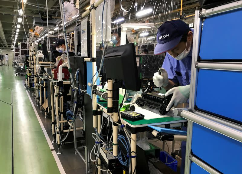 FILE PHOTO: A Ricoh employee checks a drum unit on the production line at the company's printer components factory in Atsugi