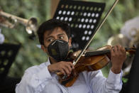 A musician plays during a tribute by health workers at the San Juan de Dios hospital in memory of their colleagues who died from COVID-19, at the hospital in Guatemala City, Friday, Oct. 9, 2020. (AP Photo/Moises Castillo)