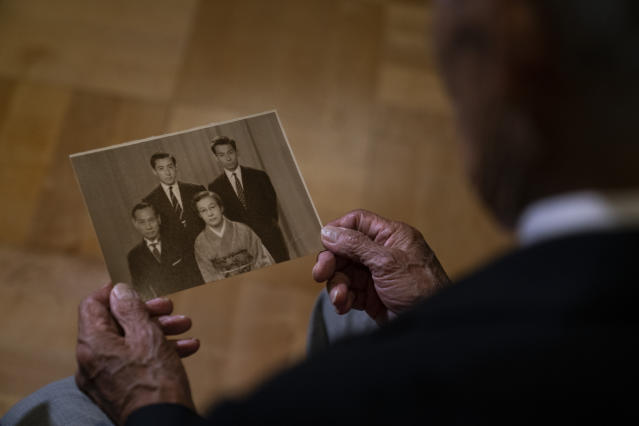In this July 8, 2019, photo, Kazuo Oda, a son of Mikio Oda, who won Japan's first Olympic gold medal and Asia's first individual gold medal at the 1928 Amsterdam Olympics, holds an old family photo during an interview with The Associated Press at Edo-Tokyo Museum in Tokyo. My father was from Hiroshima, so there was a celebration in his hometown upon his return, Kazuo Oda said. But as there were no media possibilities like today, his achievements were not known by everybody in Japan. (AP Photo/Jae C. Hong)