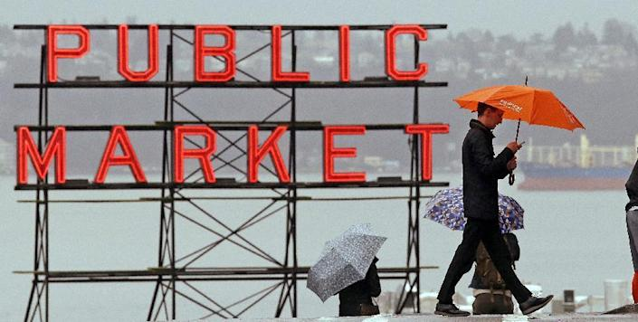 Pedestrians huddle under umbrellas as they walk past the Pike Place Market and in view of Elliot Bay behind, Wednesday, Jan. 18, 2017, in Seattle. Freezing rain, ice and fallen trees forced the closure of highways and roads in Oregon and Washington on Wednesday. Interstate 90, the main highway connecting western and eastern Washington, was to remain closed over Snoqualmie Pass until at least Thursday morning because of hazardous winter conditions. (AP Photo/Elaine Thompson)