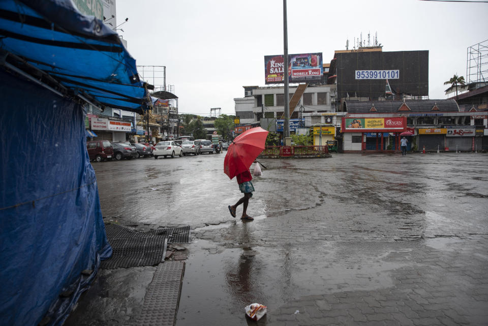 A man walks in the rain as vehicles stayed off the roads during a nation-wide shutdown to protest against the contentious farm laws in Kochi, Kerala state, India, Monday, Sept.27, 2021. (AP Photo/R S Iyer)