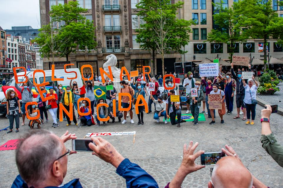 A group of Brazilian people is holding letters build the sentence Bolsonar Genocida, during a worlwide demonstration against Bolsonaro's government held in Amsterdam, Netherlands on June 19th 2021. (Photo by Romy Arroyo Fernandez/NurPhoto via Getty Images)