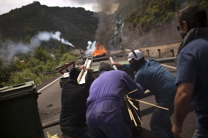 Miners fire handmade rockets at riot police officers as they defend their position after blocking a road in Cinera, near Leon, Spain, Tuesday, June 19, 2012. Striking Spanish coal miners firing homemade rockets and using slingshots have clashed with authorities in northern Spain, driving officers out a town where the miners cut off a highway and railroad service. (AP Photo/Emilio Morenatti)