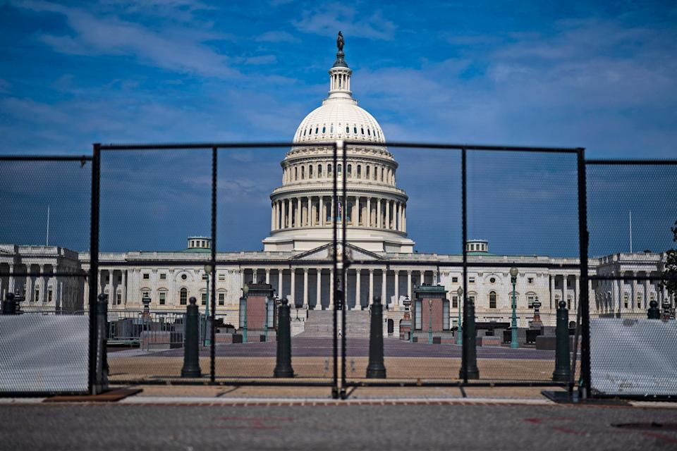 The front of the US Capitol building seen through protective barriers.