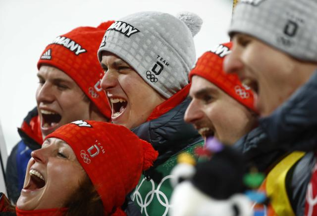 Ski Jumping - Pyeongchang 2018 Winter Olympics - Men's Team Final - Alpensia Ski Jumping Centre - Pyeongchang, South Korea - February 19, 2018 - Silver medalists Karl Geiger, Stephan Leyhe, Richard Freitag and Andreas Wellinger of Germany celebrate with a fan during the victory ceremony. REUTERS/Dominic Ebenbichler