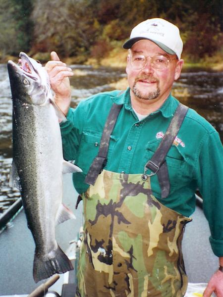 In this undated photo provided by Steve Steele, Stan Steele holds a hatchery steelhead caught on the Alsea River outside Waldport, Ore. A growing body of evidence indicates that wild fish, which must be returned to the river unharmed, are more likely to bite than hatchery fish, which end up on the barbecue. Prompted by fishermen like Steele, the Oregon Hatchery Research Center plans to conduct an experiment to see if they can breed hatchery fish to be better biters. (AP Photo/Steve Steele)