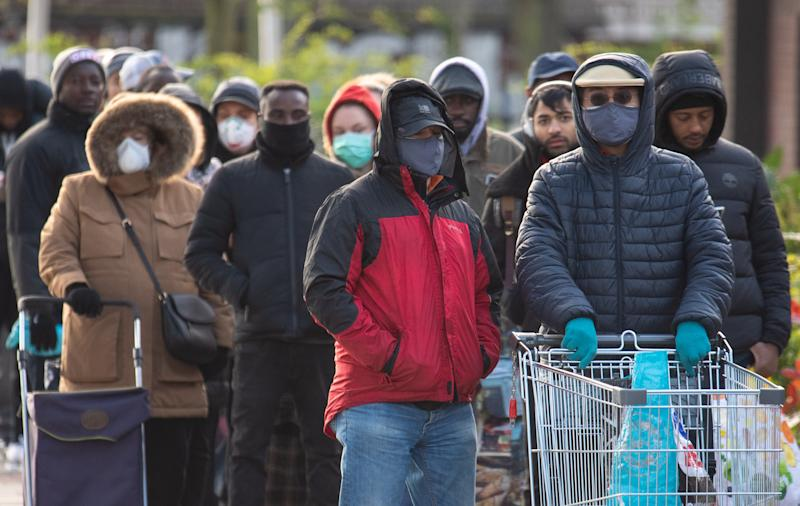 People queue outside a branch of Aldi in south London, a day after the Chancellor unveiled an emergency package aimed at protecting workers' jobs and wages as they face hardship in the fight against the coronavirus pandemic.