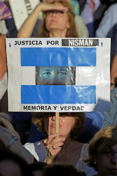 "A woman holds a sign reading ""Justice for Nisman! Memory and Truth"" during a vigil on the first anniversary of the prosecutor's mysterious death in January 2016 (AFP Photo/Eitan ABRAMOVICH)"