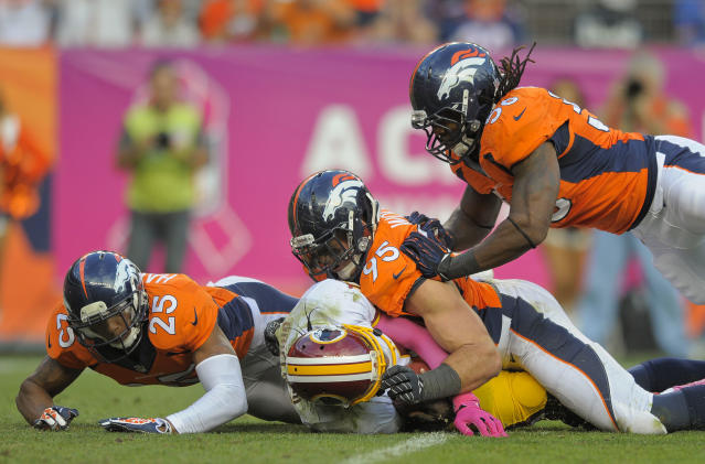 Denver Broncos cornerback Chris Harris (25), defensive end Derek Wolfe (95) and outside linebacker Nate Irving (56) pile on top of Washington Redskins quarterback Robert Griffin III (10) for a sack in the fourth quarter of an NFL football game, Sunday, Oct. 27, 2013, in Denver. The Broncos won 45-21. (AP Photo/Jack Dempsey)