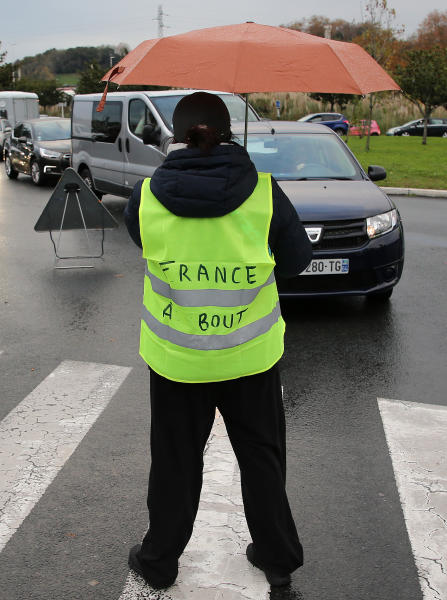 """A demonstrator wears a jacket that reads: """"France is Exhausted"""" as he block cars in Bayonne, southwestern France, Sunday, Nov. 18, 2018. One protester was killed and 227 other people were injured — eight seriously — at roadblocks set up around villages, towns and cities across France on Saturday as citizens angry with rising fuel taxes rose up in a grassroots movement, posing a new challenge to beleaguered President Emmanuel Macron. (AP Photo/Bob Edme)"""