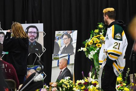 Humboldt Broncos' Nick Shumlanski, who was released from hospital earlier today, looks at photographs of other victims during a vigil at the Elgar Petersen Arena, home of the Humboldt Broncos, to honour the victims of a fatal bus accident in Humboldt, Saskatchewan, Canada April 8, 2018. Jonathan Hayward/Pool via REUTERS