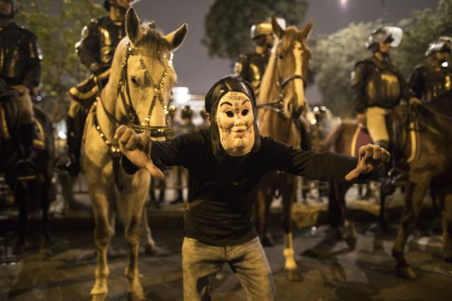 A masked supporter of President Martin Vizcarra gives a thumbs down outside Congress where horse-mounted police stand guard after the president dissolved the legislature in Lima, Peru, Monday, Sept. 30, 2019. Vizcarra dissolved congress Monday, exercising seldom used executive powers to shut down the opposition-controlled legislature that he accuses of stonewalling attempts to curb widespread corruption. (AP Photo/Rodrigo Abd)