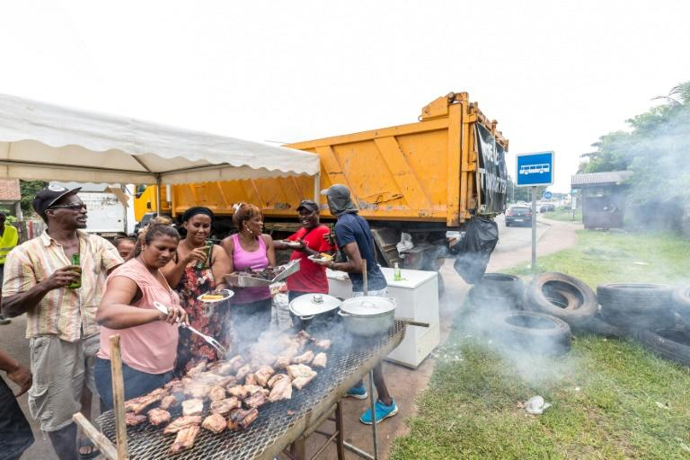 People eat at a barbecue at a road block in Cayenne, French Guiana, during a string of region-wide protests and road blockades