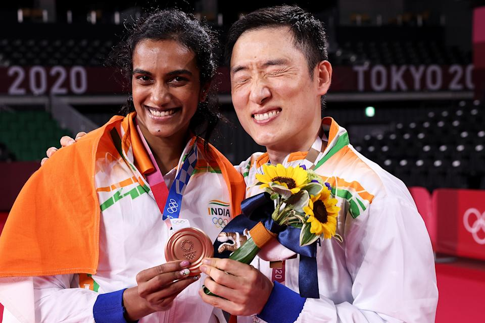 CHOFU, JAPAN - AUGUST 01: Bronze medalist Pusarla V. Sindhu of Team India poses for camera with her coach Park Tae-sang(right) during the medal ceremony for the Women's Singles badminton event on day nine of the Tokyo 2020 Olympic Games at Musashino Forest Sport Plaza on August 01, 2021 in Chofu, Tokyo, Japan. (Photo by Lintao Zhang/Getty Images)