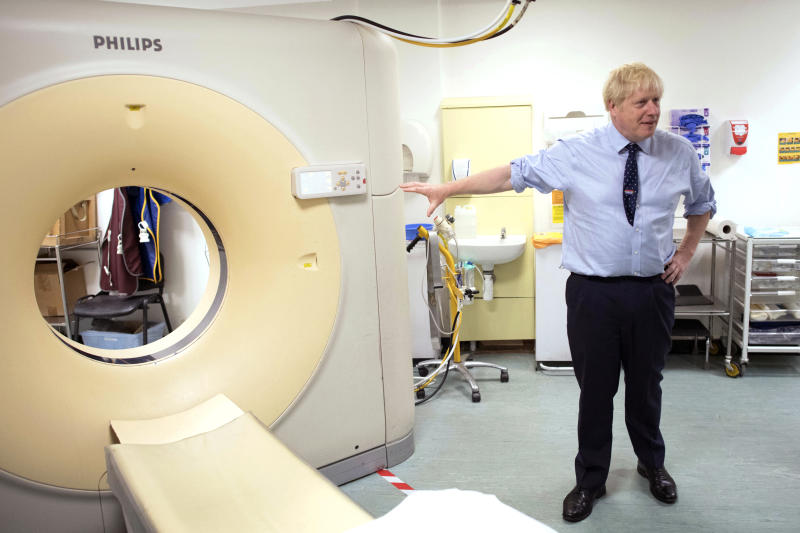 British Prime Minister Boris Johnson meets staff and sees an MRI CT Scanner during a visit to The Princess Alexandra hospital in Harlow, England, Friday, Sept. 27, 2019. Dominic Cummings, senior adviser to British Prime Minister Boris Johnson, has dismissed concerns that politicians' heated rhetoric over Brexit is polarizing society, telling supporters that it isn't surprising that people are upset about the country's failure to leave the European Union. (Stefan Rousseau/Pool Photo via AP)