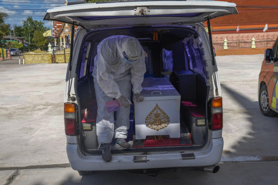 A Siam Nonthaburi Foundation volunteer in full a protective suit sprays disinfect on a coffin containing a COVID-19 victim for a free funeral ceremony service at Wat Ratprakongtham temple Nonthaburi Province, Thailand, Monday, July 12, 2021. Wat Ratprakongtham temple offering free funeral service for people dying from COVID-19 says it is struggling to keep up with 24-hour cremation, and is adding another crematorium as Thailand sees a growing number of cases and deaths in a coronavirus surge that began in early April. (AP Photo/Sakchai Lalit)