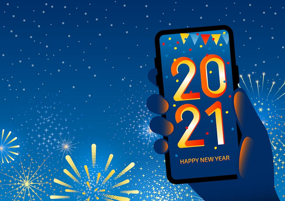 Hand holding a smartphone which displays a 2021 Happy New Year with confetti and decoration. Celebration with fireworks is in the background. There is space for your text, message.