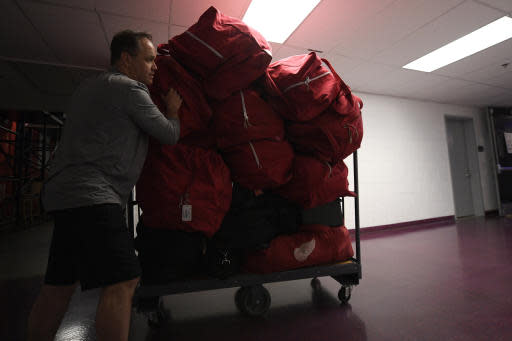 Paul Boyer, head equipment manager of The Detroit Red Wings NHL hockey team, wheels out equipment bags in the hallway of Capital One Arena, Thursday, March 12, 2020, in Washington. (AP Photo/Nick Wass)