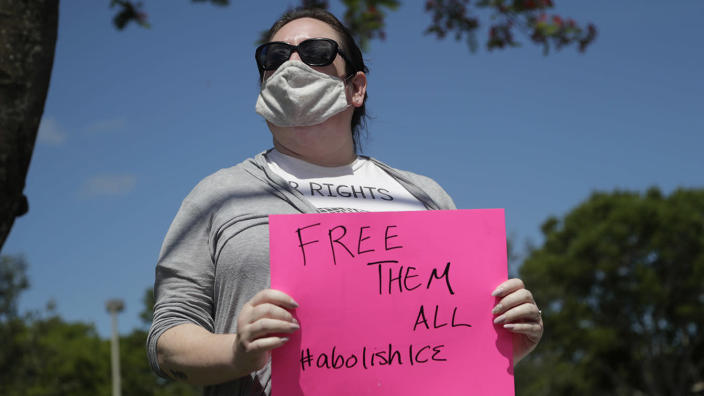 Sarah Bosch-McGuinn wears a protective face mask as she protests outside of a U.S. Immigration and Customs Enforcement field office during the new coronavirus pandemic, Friday, May 29, 2020, in Plantation, Fla. (Lynne Sladky/AP)