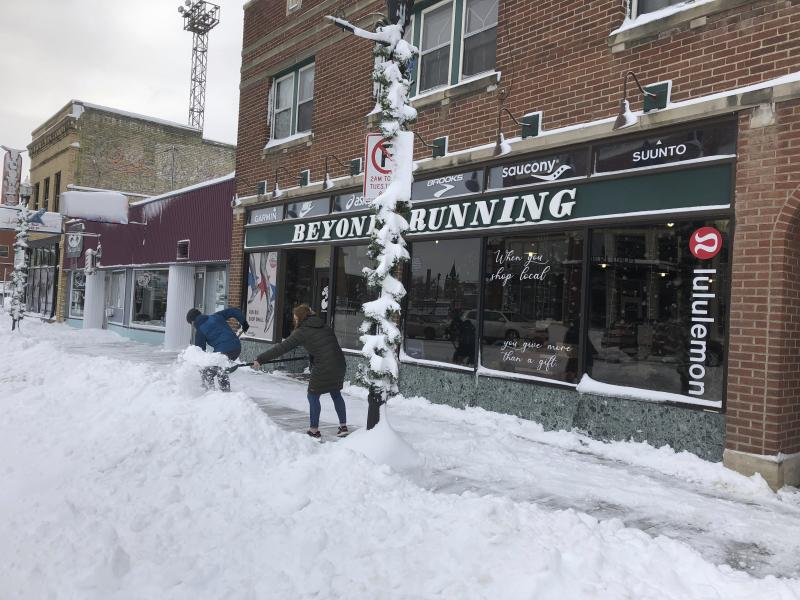 Jake Olson, left, and Mackenzie Weinberger shovel snow outside of a store in downtown Fargo, N.D. on Monday, Dec. 30, 2019, following a blizzard that dropped over a foot of snow in the area and closed streets, highways and many businesses. Fargo Mayor Tim Mahoney said the storm was one of the worst he's seen because it began with a sheet of ice and ended with 40 mph wind gusts. Mahoney asked residents to be patient and help their neighbors. (AP Photo/Dave Kolpack)