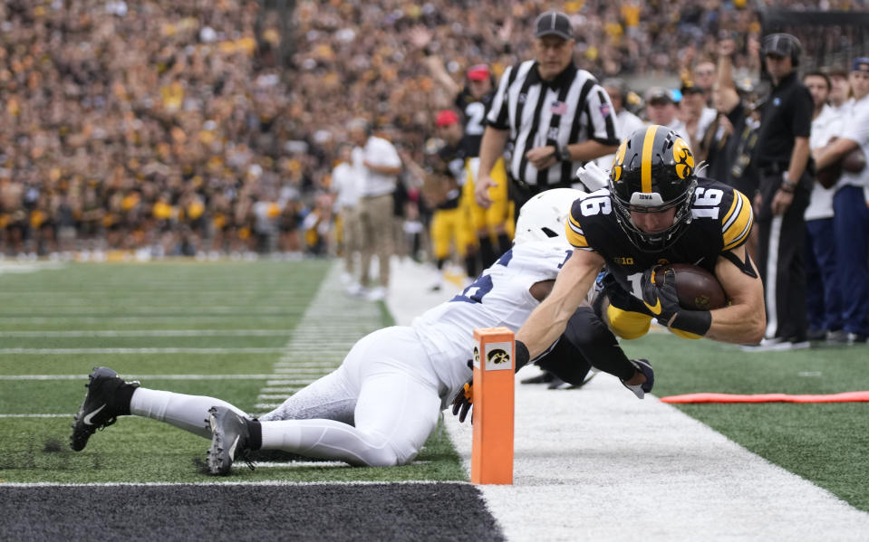 Iowa wide receiver Charlie Jones (16) dives for a touchdown despited defensive efforts by Penn State safety Ji'Ayir Brown (16) during the first half of an NCAA college football game, Saturday, Oct. 9, 2021, in Iowa City, Iowa. (AP Photo/Matthew Putney)