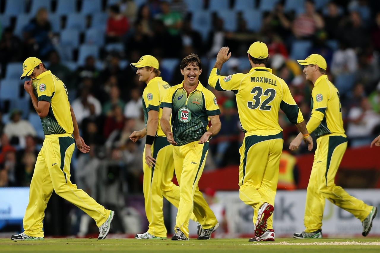 Australia cricket players celebrate the dismissal of South Africa's AB de Villiers after he was caught out by Brad Hogg during the final of the T20 cricket test match in Centurion, March 14, 2014. REUTERS/Siphiwe Sibeko (SOUTH AFRICA - Tags: SPORT CRICKET)