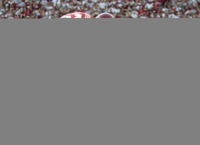 """FILE - In this Oct. 1, 2005, file photo, Alabama trainers work on Tyrone Prothro as quarterback Brodie Croyle pats him on the back after he broke his leg on an incomplete pass-play in an NCAA college football game against Florida in Tuscaloosa, Ala. Prothro made a play so spectacular it's known in Alabama as """"The Catch,"""" immortalized both in photos and an advertising campaign by automaker Pontiac. But when it came time a few years ago to get surgery on the leg he broke during a 2005 game his 10th surgery for the injury he was told by a trainer that his college benefits were about to run out. (AP Photo/Rob Carr, File)"""