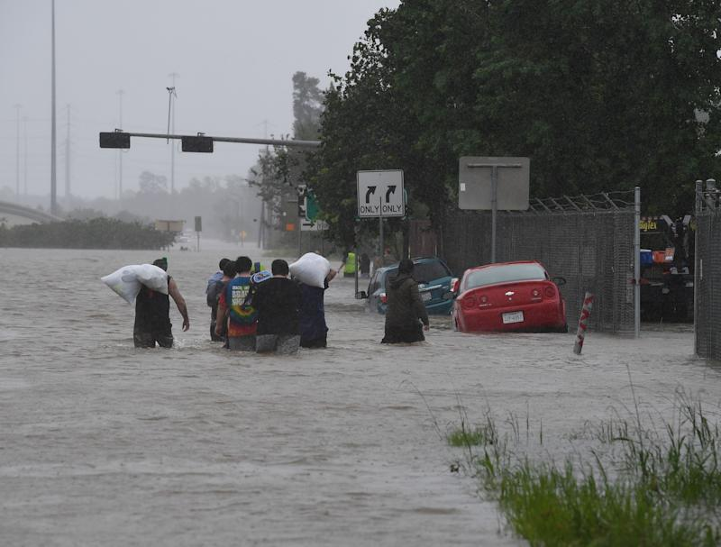 People walk through water to escape from their homes on Highway 90 after Hurricane Harvey caused heavy flooding in Houston, Texas on Aug. 28, 2017.