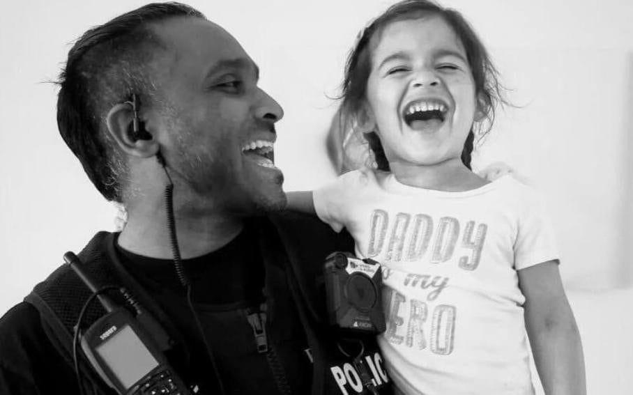 Police Constable Abbasuddin Ahmed with his daughter - Greater Manchester Police / PA