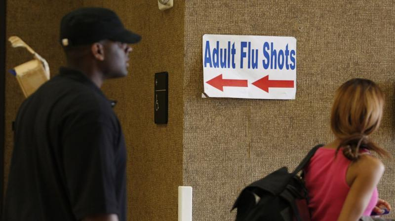 People walk past a sign advertising adult flu shots inside the Dallas County Department of Health and Human Services building in Dallas
