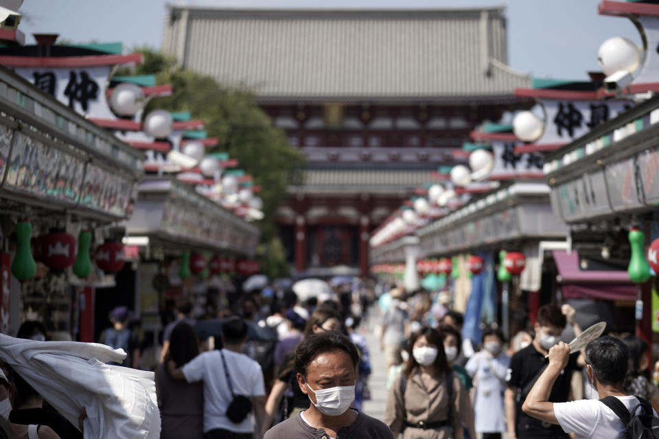 Visitors wearing protective masks to help curb the spread of the coronavirus walk at shopping arcade at in Asakusa district Friday, Aug. 14, 2020, in Tokyo. The Japanese capital confirmed more than 380 coronavirus cases on Friday. (AP Photo/Eugene Hoshiko)