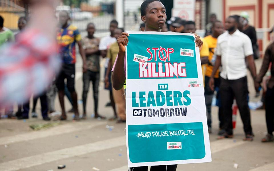 A boy holds a banner during a protest against the Nigeria rogue police - AKINTUNDE AKINLEYE/EPA-EFE/Shutterstock