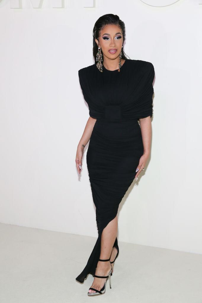<p>Cardi B arrives for Tom Ford's spring/summer 2019 fashion show wearing a black ruched jersey evening dress by the designer on Sept. 5, 2018, in New York City. (Photo: Rob Kim/WireImage) </p>