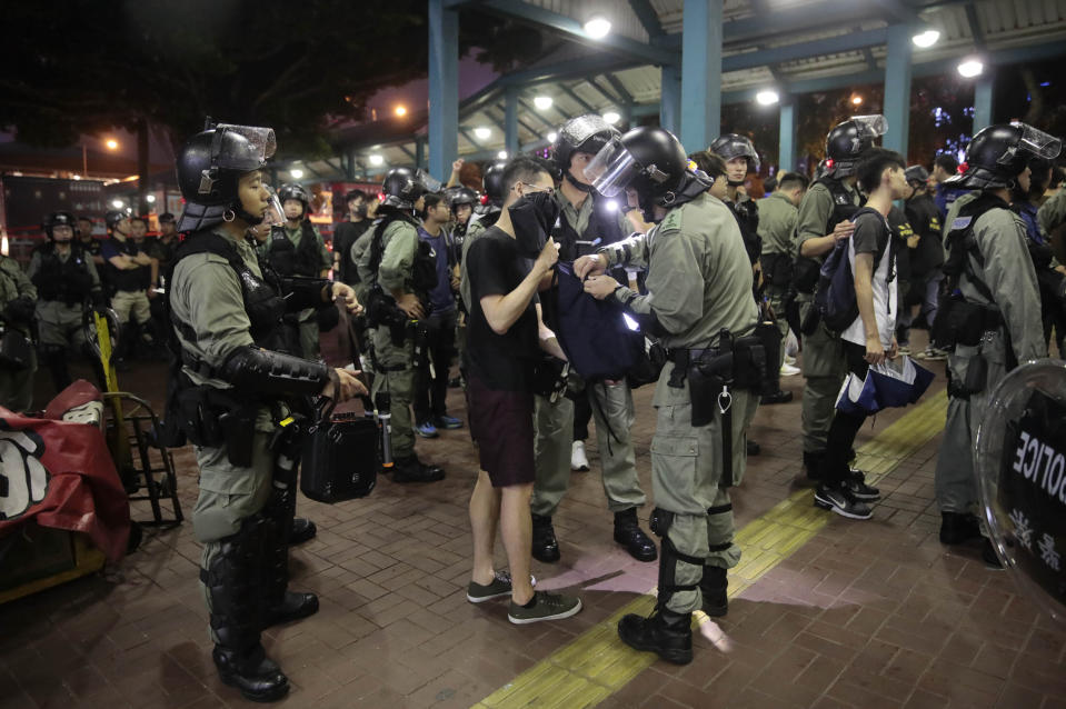 Police search people who got off a ferry at central ferry pier in Hong Kong, Sunday, Sept. 1, 2019. Train service to Hong Kong's airport was suspended Sunday as pro-democracy demonstrators gathered there, while protesters outside the British Consulate called on London to grant citizenship to people born in the former colony before its return to China. (AP Photo/Jae C. Hong)