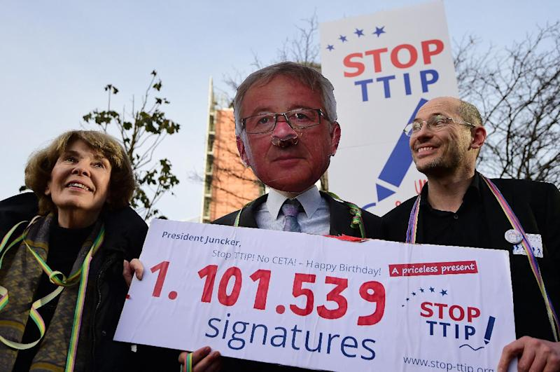 An activist wearing a mask of European Commission President Jean-Claude Juncker protests against the US-EU Transatlantic Trade and Investment Partnership (TTIP) in Brussels, on December 9, 2014