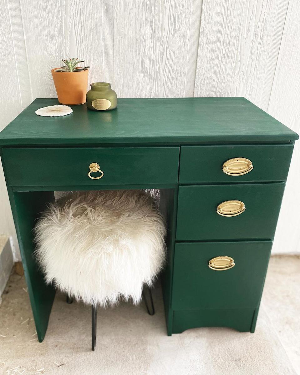 A small vintage bottle green desk with three drawers and gold drawer pulls