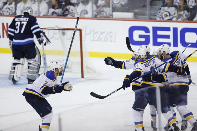 St. Louis Blues celebrate Tyler Bozak's goal against the Winnipeg Jets during the third period of Game 1 of an NHL hockey first-round playoff series Wednesday, April 10, 2019, in Winnipeg, Manitoba. Bozak is second from right, eyes and helmet visible. (John Woods/The Canadian Press via AP)