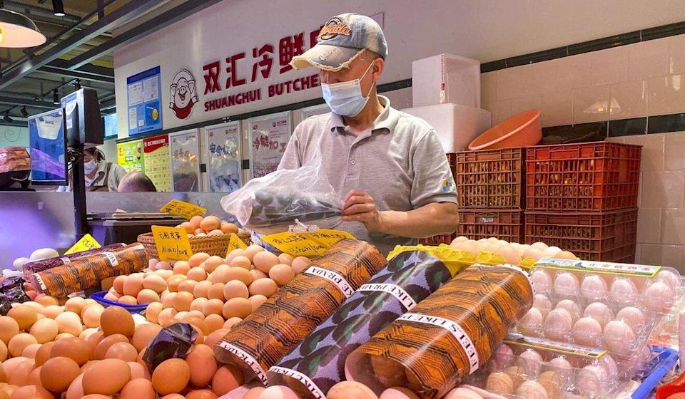 A merchant at Wuzhong wet market in Shanghai sells chicken eggs packaged with Prada wrapping paper. Photo: SCMP/ Daniel Ren