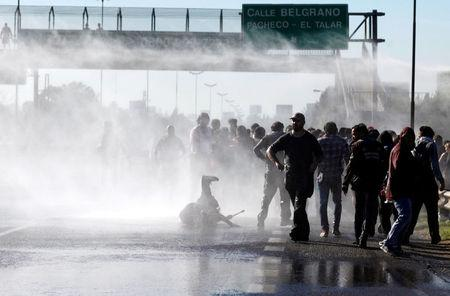 Protestors are sprayed with water by Argentine police as they block a road during a 24-hour national strike in Buenos Aires, Argentina, April 6, 2017. REUTERS/Martin Acosta